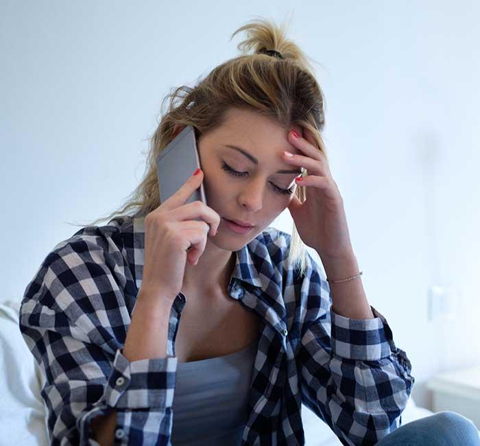 Junge Frau spricht nachdenklich am Telefon